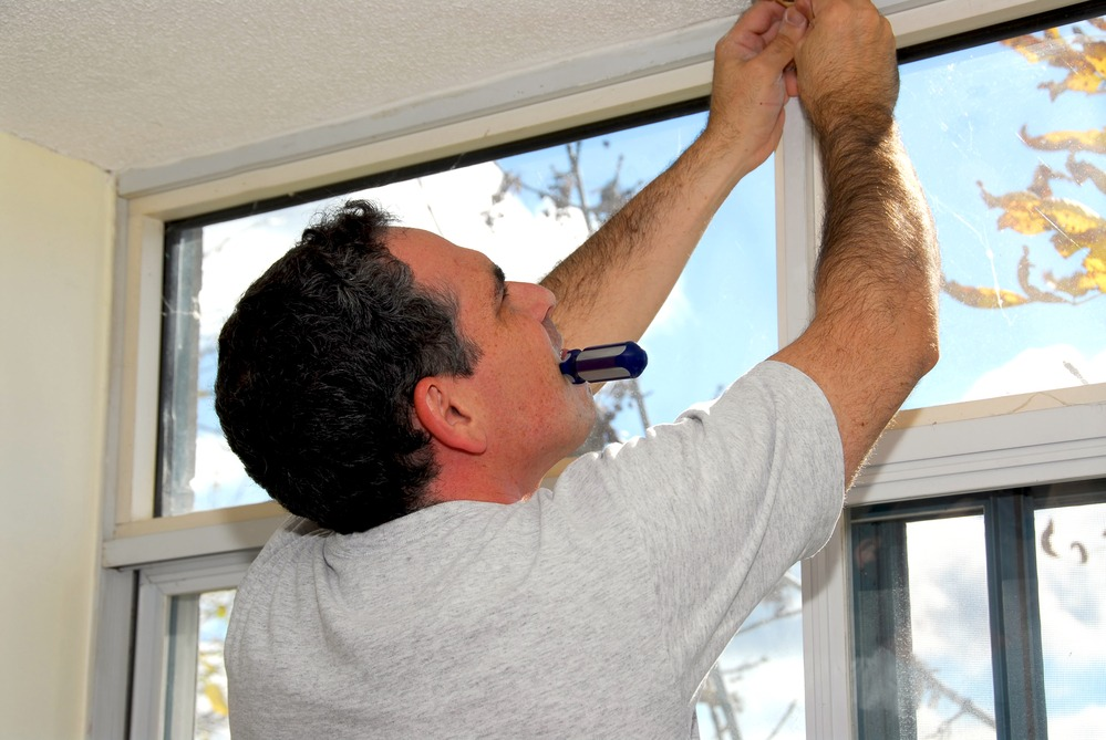 Man installing window blinds in a house